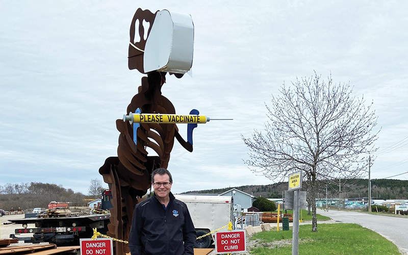 President and owner John Bourque, standing outside with the fabricated T-Rex
